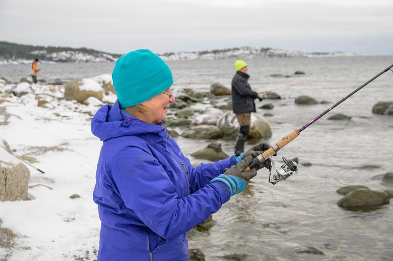 Bild på personer som vinterfiskar vid stranden